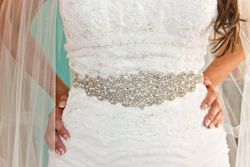 Kvinna med brudklänningen med bältet royaltyfria bilder