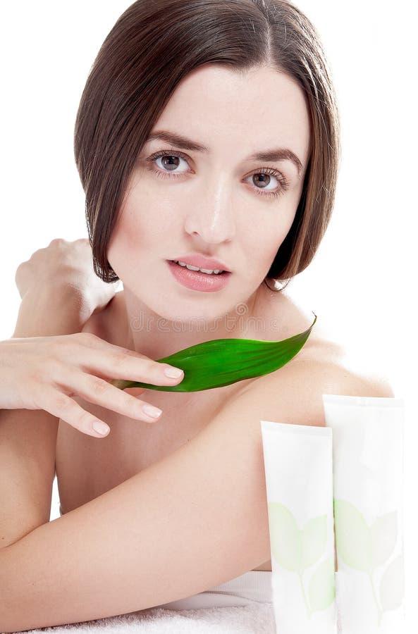 Kvinna med brunn-ansad hud nära organiska skönhetsmedel. royaltyfria bilder