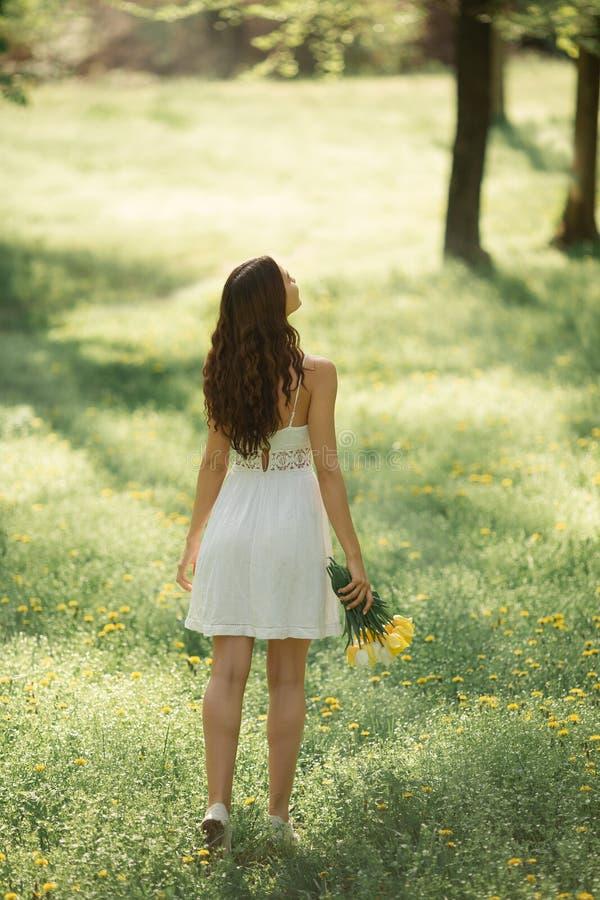 Kvinna med buketten av vårblommorna utomhus arkivfoto