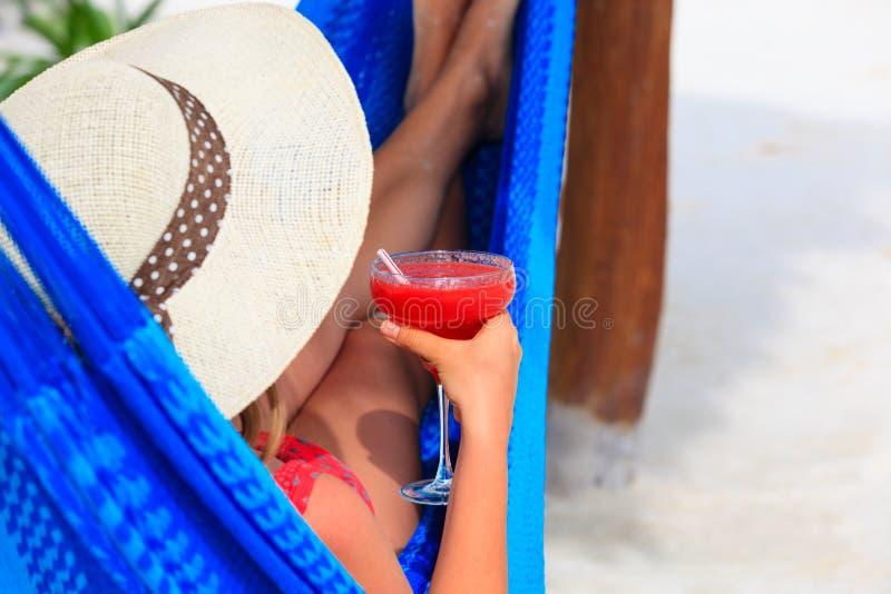 Kvinna med coctailen som kopplas av på den tropiska stranden royaltyfria foton