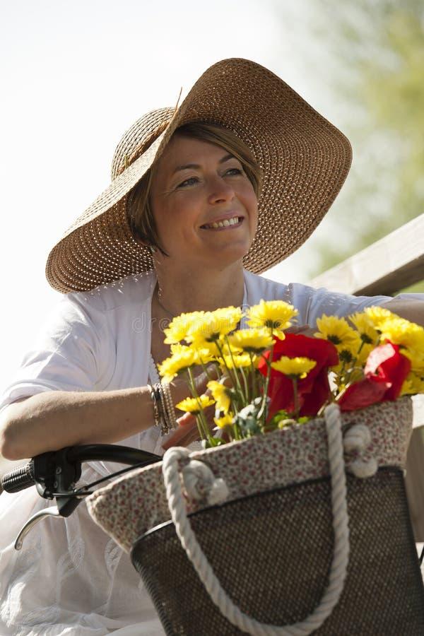 Kvinna med cykeln och blommor arkivfoto
