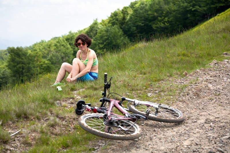 Kvinna med cykeln på vila arkivfoto