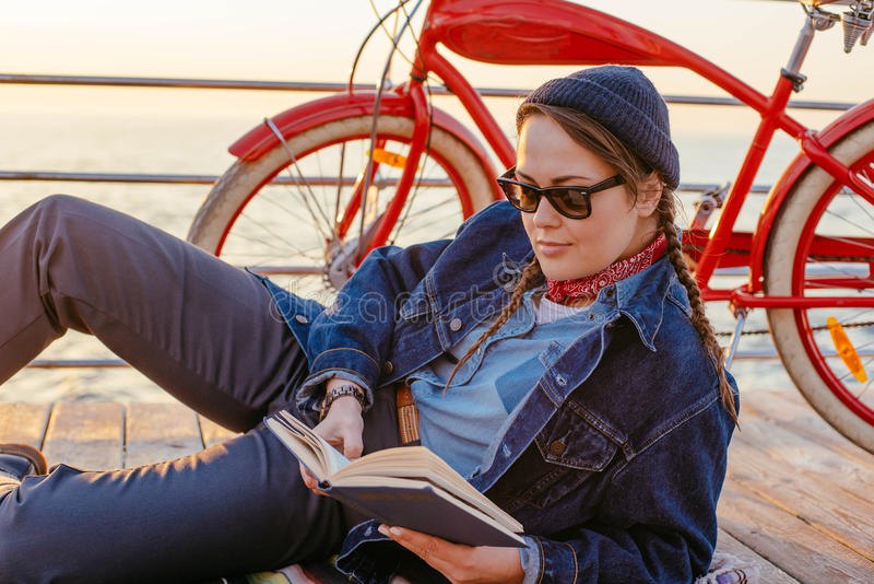 Kvinna med cykeln som vilar på sjösidan fotografering för bildbyråer