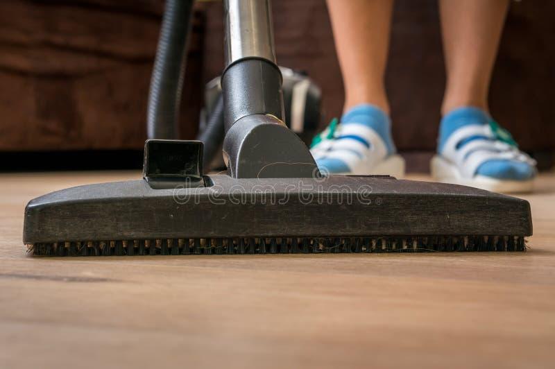 Kvinna med dammsugare som gör ren trälaminatgolvet royaltyfri foto