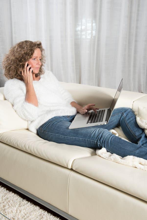 Kvinna med datoren på soffan som har en påringning royaltyfri fotografi