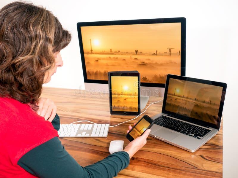 Kvinna med datorer och mobila enheter arkivbilder