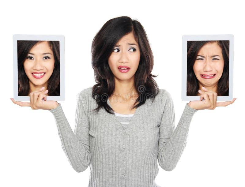 Kvinna med datorskärmen för två minnestavla en med att le framsidan och arkivbild
