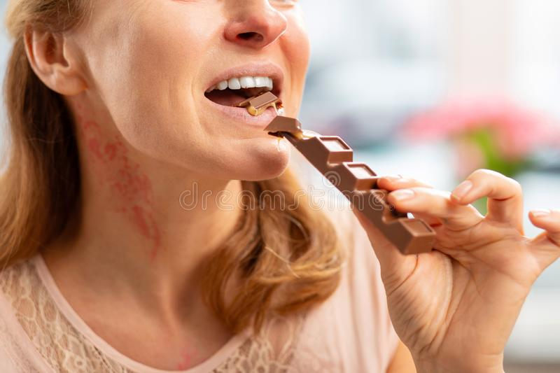 Kvinna med den överilade och rodna halsen som äter chokladstången royaltyfri bild