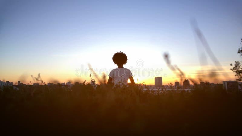 Kvinna med den afro frisyren som tycker om solnedgången, kännande energi av solen, meditation arkivbild