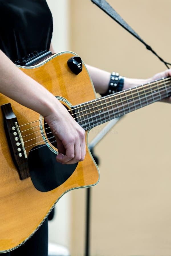 Kvinna med den akustiska gitarren som utför i gatakonsert fotografering för bildbyråer