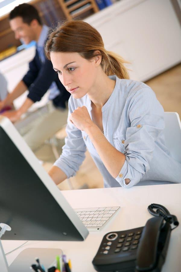 Kvinna med den allvarliga blicken som arbetar på datoren royaltyfri bild