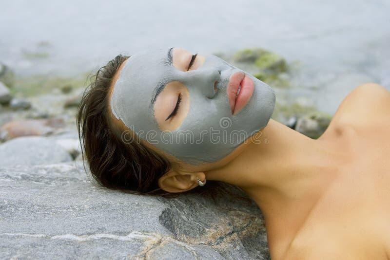 Kvinna med den ansikts- maskeringen för blå lera i skönhetbrunnsorten (wellnessen) royaltyfri fotografi