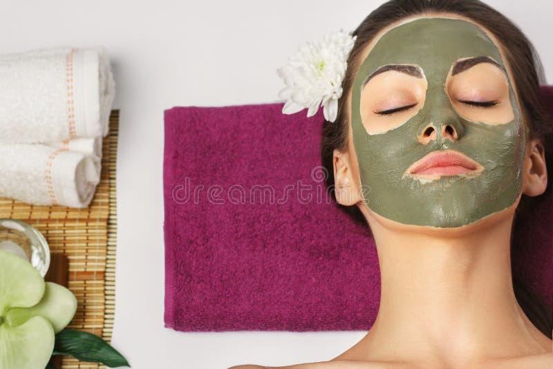 Kvinna med den ansikts- maskeringen f?r lera i sk?nhetbrunnsort Skincare p?rlor f?r bl? f?r begrepp f?r bakgrundssk?nhet blir gru fotografering för bildbyråer
