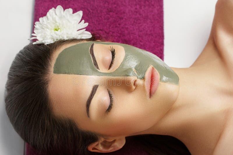 Kvinna med den ansikts- maskeringen f?r lera i sk?nhetbrunnsort Skincare p?rlor f?r bl? f?r begrepp f?r bakgrundssk?nhet blir gru arkivfoto