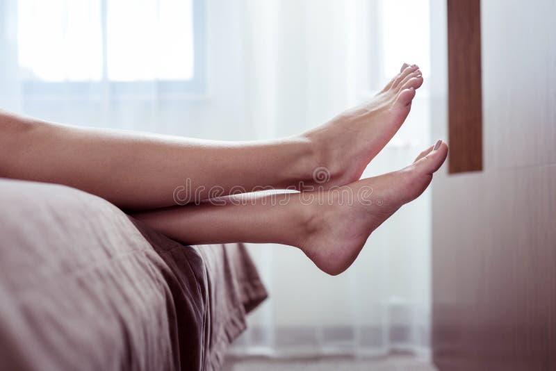 Kvinna med den beigea pedikyren som ligger på trevlig stor dubbelsäng i hotellrum arkivfoto