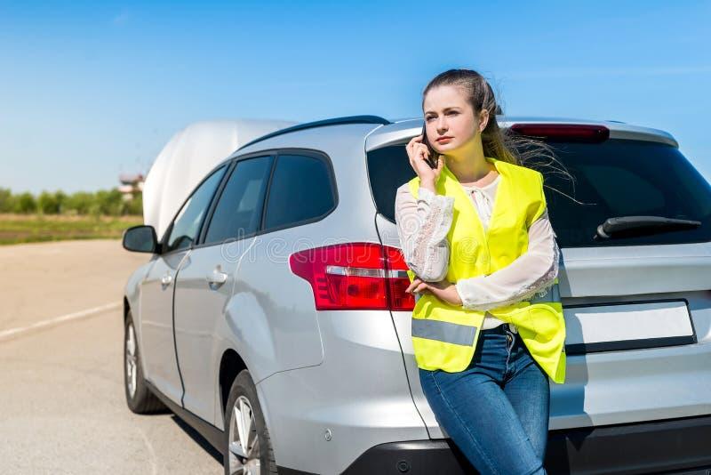 Kvinna med den brutna bilen som kallar för hjälp royaltyfria foton