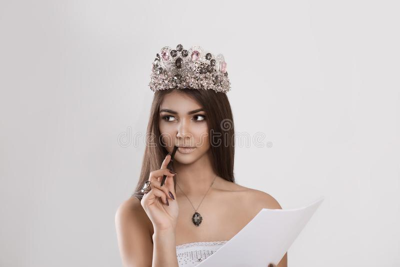 Kvinna med den crystal kronan som ser tänka upp analysera hållande legitimationshandlingardokument royaltyfri foto