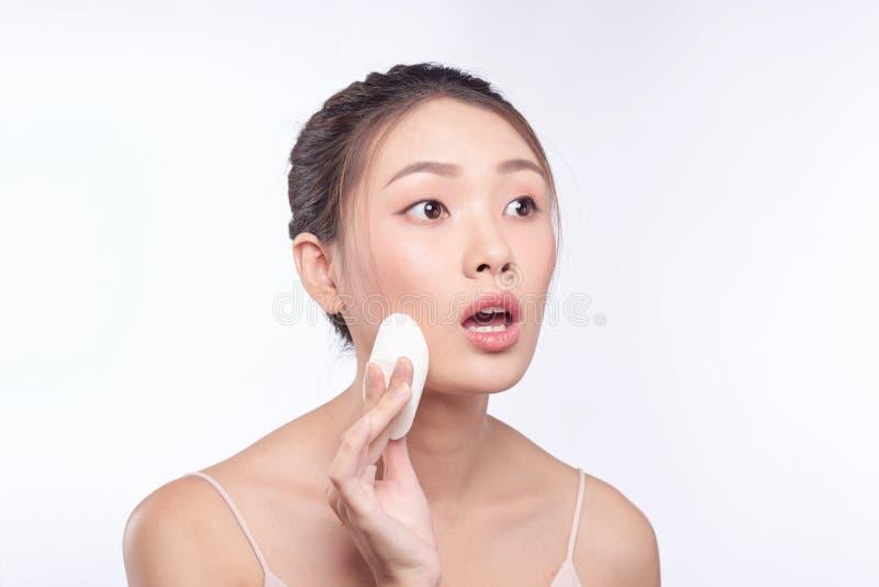 Kvinna med den förvånade framsidan som sätter på sminket, applicerat vätskefundament på hennes framsida royaltyfria bilder