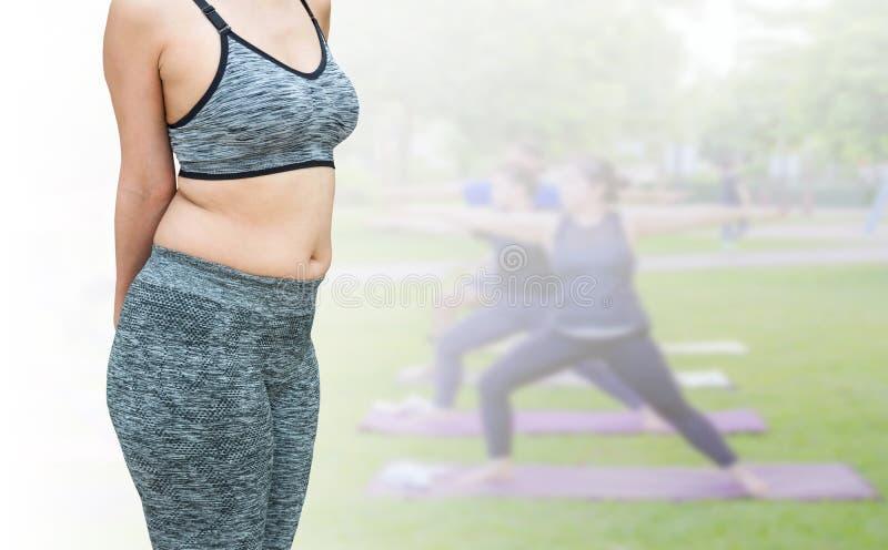 kvinna med den feta bärande sportswearen för buk som förbereder sig för yogaisolator arkivbilder