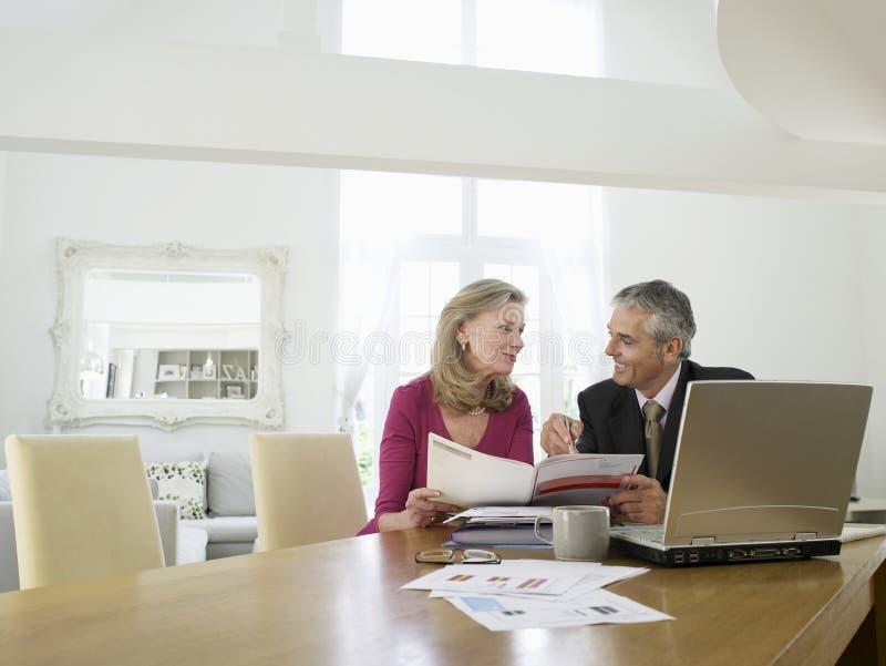 Kvinna med den finansiella rådgivaren på tabellen royaltyfri fotografi