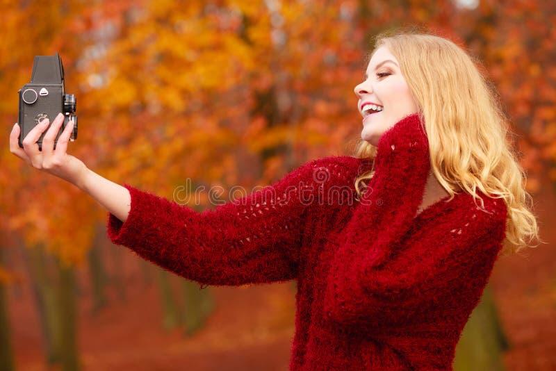 Kvinna med den gamla tappningkameran som tar selfiefotoet royaltyfria foton