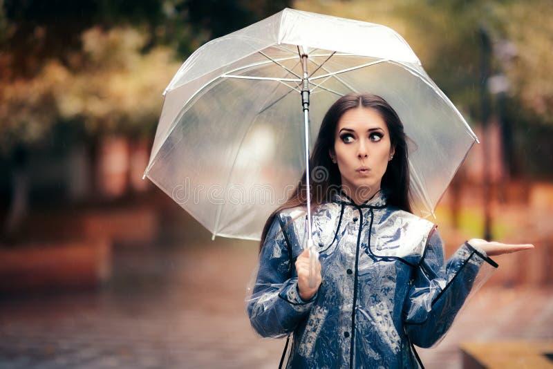 Kvinna med den genomskinliga regnrocken och paraplyet som kontrollerar för regn royaltyfria bilder