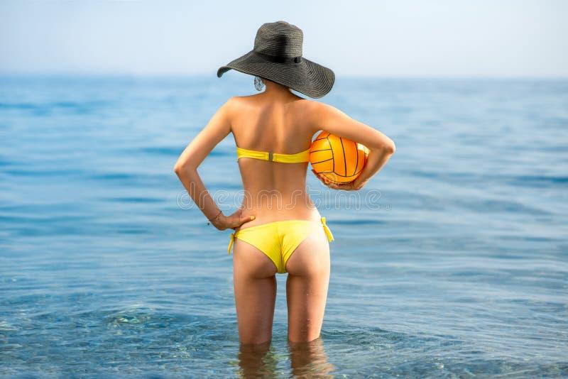 Kvinna med den gula bollen i havet royaltyfri fotografi