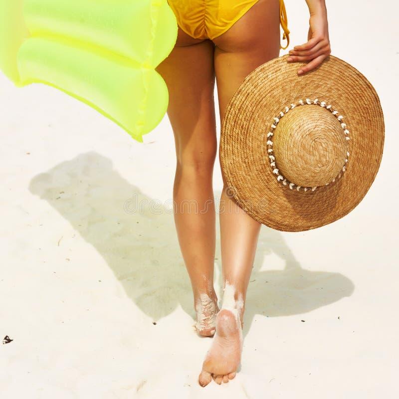 Kvinna med den gula uppblåsbara flotten på stranden royaltyfri fotografi