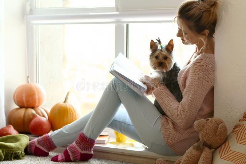 Kvinna med den gulliga hundläseboken hemma på höstdag arkivbild