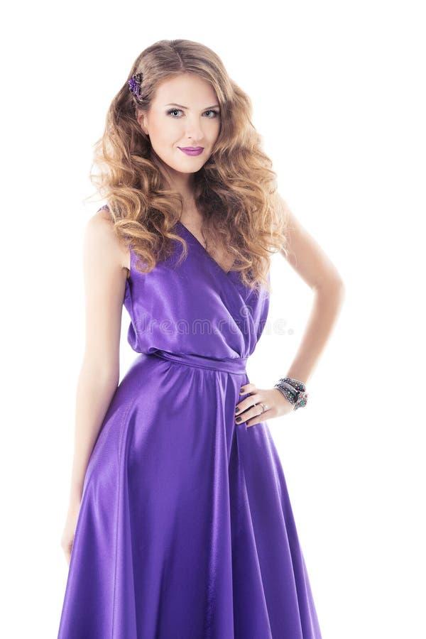 Kvinna med den härliga lockiga frisyren i purpurfärgad siden- klänning royaltyfri bild