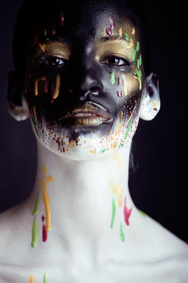Kvinna med den idérika makeupcloseupen som droppar av färger, facepaint nära övre halloween royaltyfria bilder