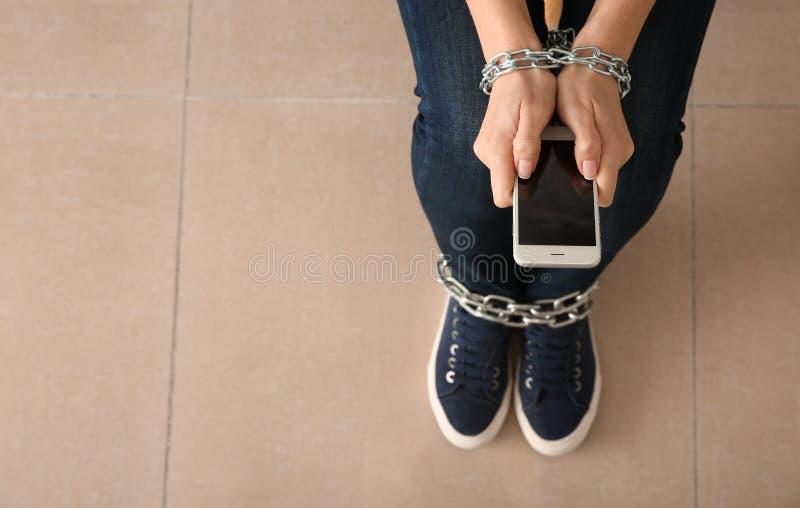 Kvinna med den kedjade fast händer och mobiltelefonen inomhus Begrepp av b?jelse arkivfoton
