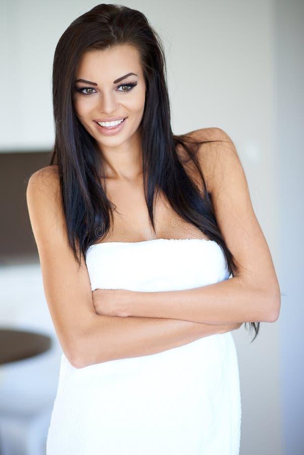 Kvinna med den långa bärande badlakanet för mörkt hår fotografering för bildbyråer