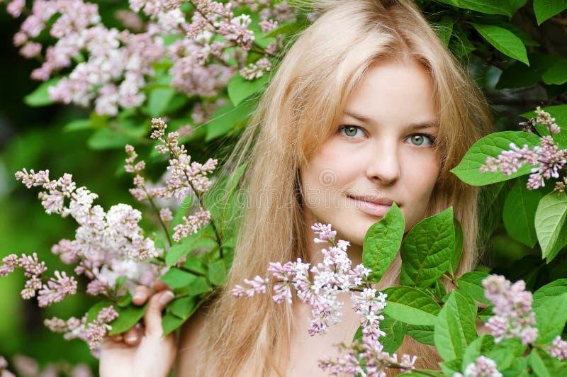 Kvinna med den lila blomman på framsida arkivfoto