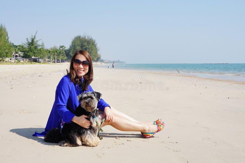 Kvinna med den lilla hunden på stranden arkivfoto
