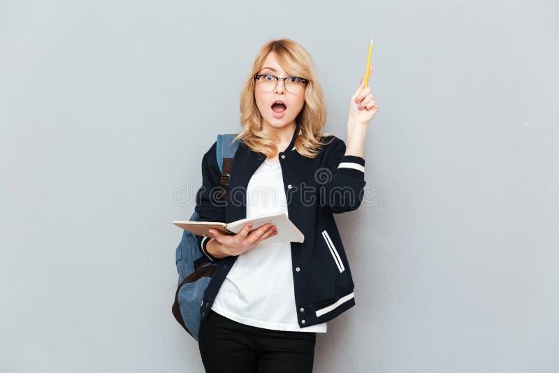Kvinna med den lyftta blyertspennan fotografering för bildbyråer