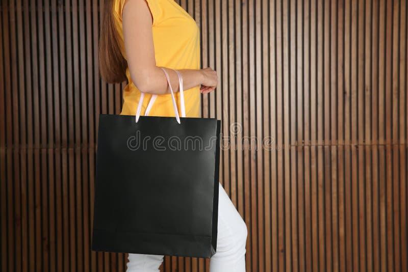 Kvinna med den pappers- shoppa påsen på träbakgrund arkivbild