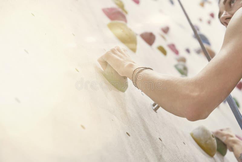Kvinna med den perfekta passformkroppen, härliga muskulösa armar som utbildar på en klättringvägg i sportkorridor royaltyfria bilder