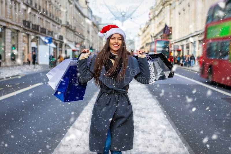 Kvinna med den röda jultomtenhatten och många shoppa påsar på Regent Street i London, UK arkivbild