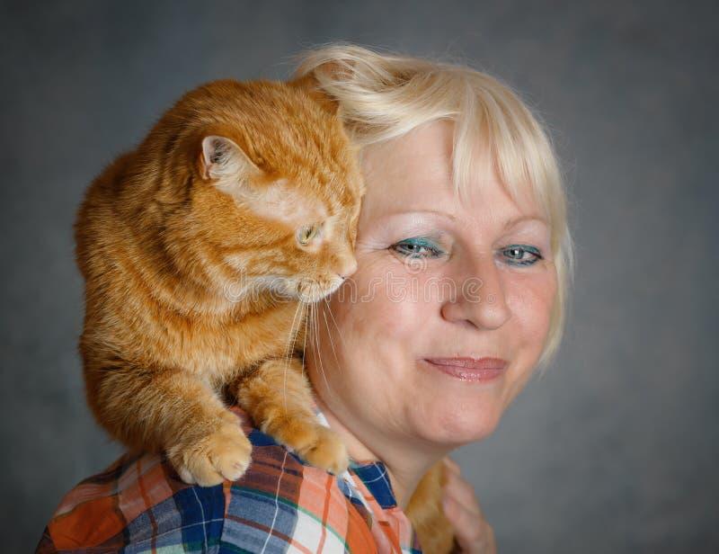 Kvinna med den röda katten arkivfoto