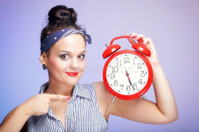 Kvinna med den röda klockan. Begrepp för Tid ledning. arkivbilder