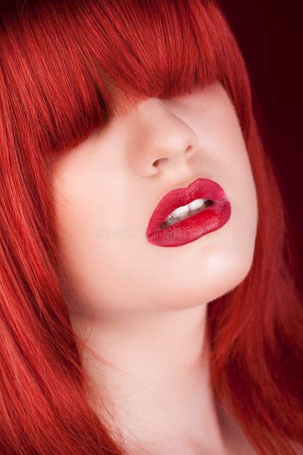 Kvinna med den röda peruken över ögat på mörker - röd bakgrund arkivbilder