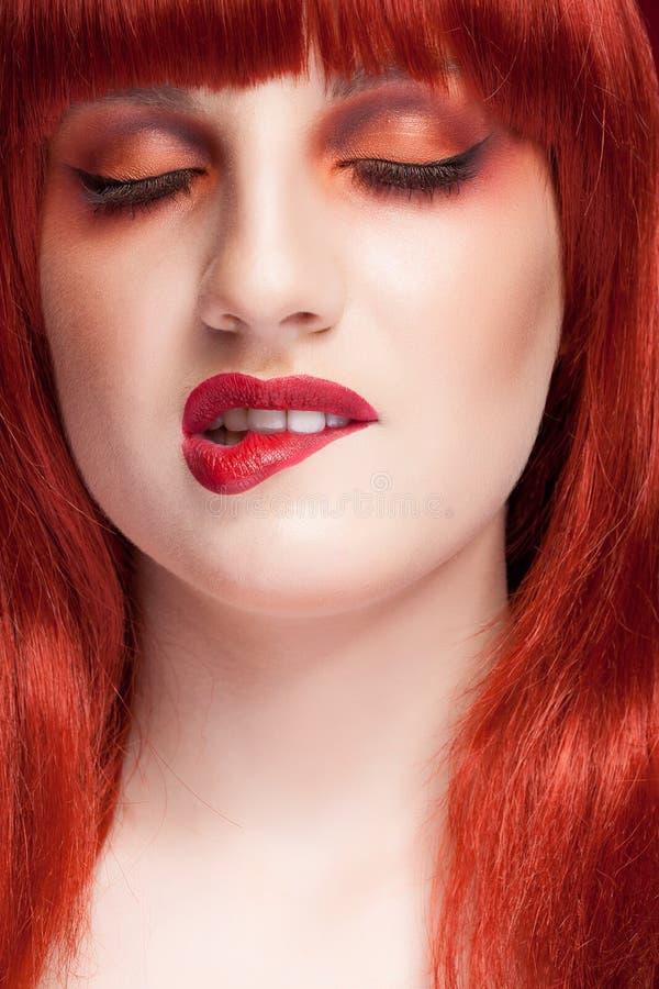 Kvinna med den röda peruken, smink och peruken royaltyfri bild