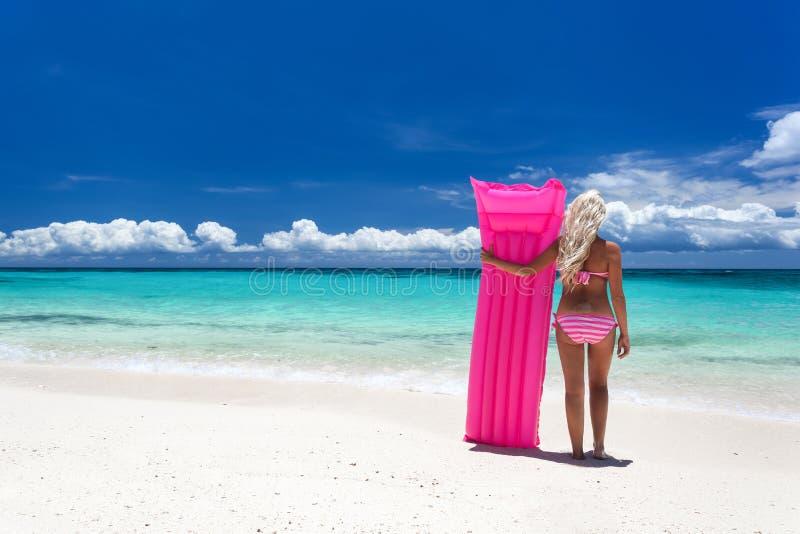 Kvinna med den rosa simningmadrassen på den tropiska stranden royaltyfria bilder