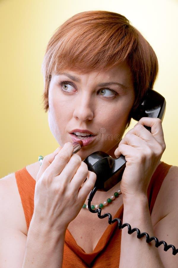 Kvinna med den roterande telefonen som applicerar läppstift arkivfoton
