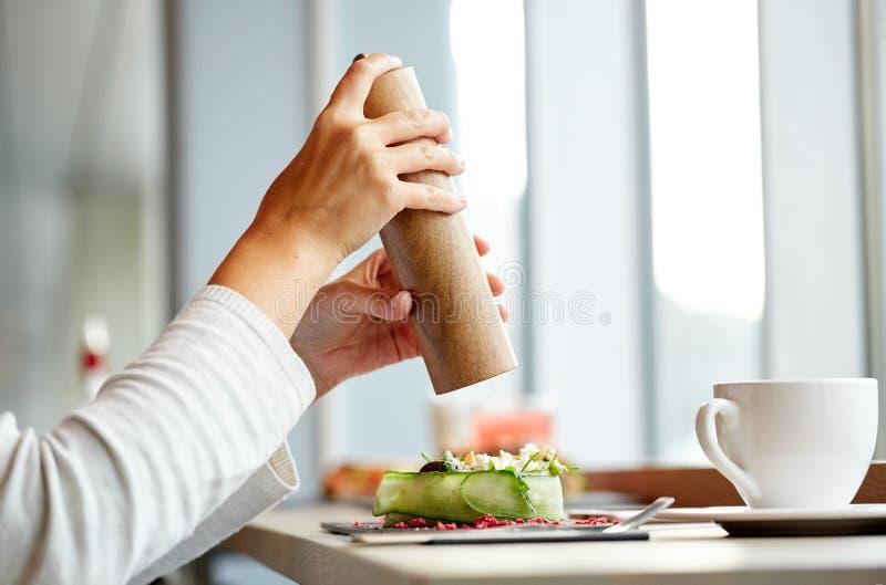 Kvinna med den salta shaker och sallad på restaurangen royaltyfri foto