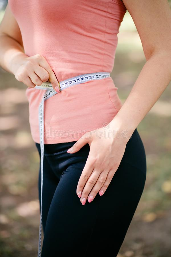 Kvinna med den slanka kroppen som mäter hennes midja royaltyfri fotografi