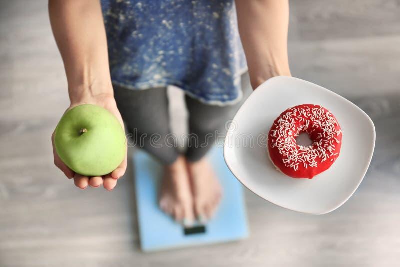 Kvinna med den smakliga munken och det nya äpplet, medan mäta hennes vikt på golvvåg Val mellan sund och sjuklig mat arkivbild