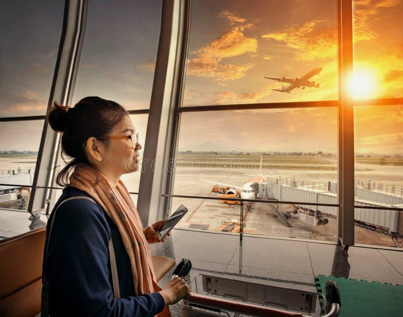 Kvinna med den smarta telefonen i handanseende i buil för flygplatsterminal royaltyfri bild