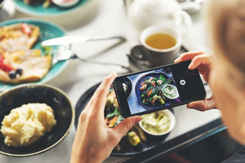 Kvinna med den smarta telefonen som tar bilden av mat på restaurangen arkivfoto